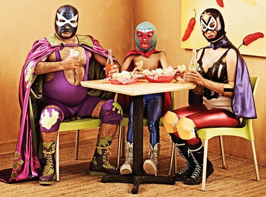 Familia de luchadores mexicanos comiendo tacos.